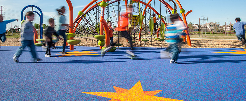 An image of children playing on an installation of PebbleFlex at Buscher Park