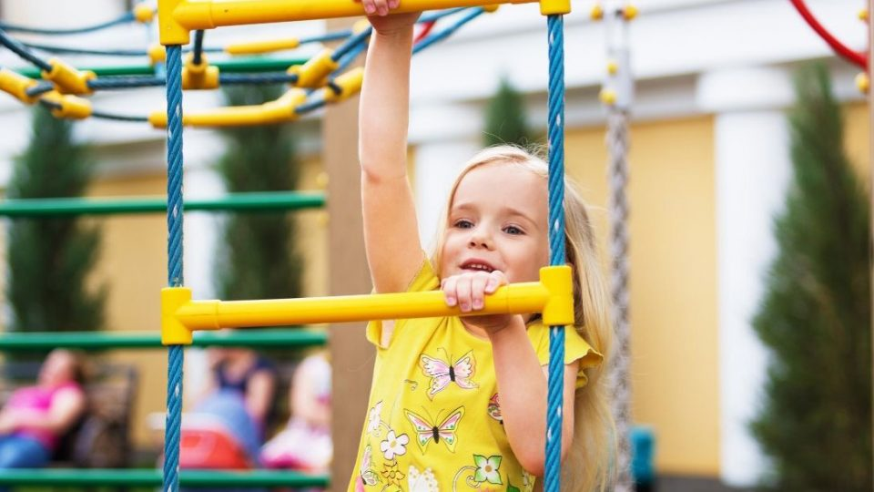 Young girl playing on playground equipment